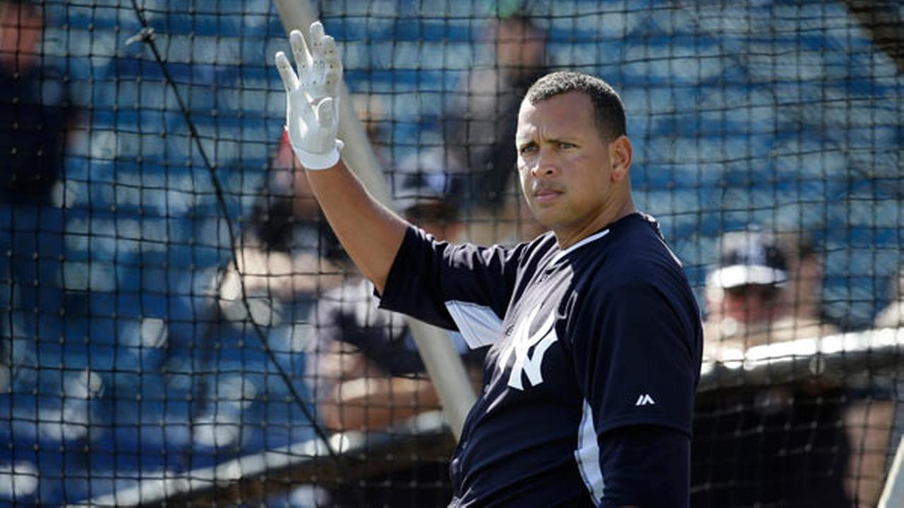 New York Yankees Alex Rodriguez waves as a fan calls out his name during batting practice before an exhibition spring training baseball game against the Philadelphia Phillies.