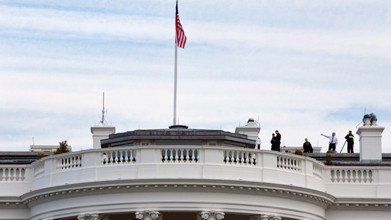 Uniformed Secret Service agents patrol the top of the White House as seen from the South Lawn of the White House in Washington, Tuesday, March 17, 2015.