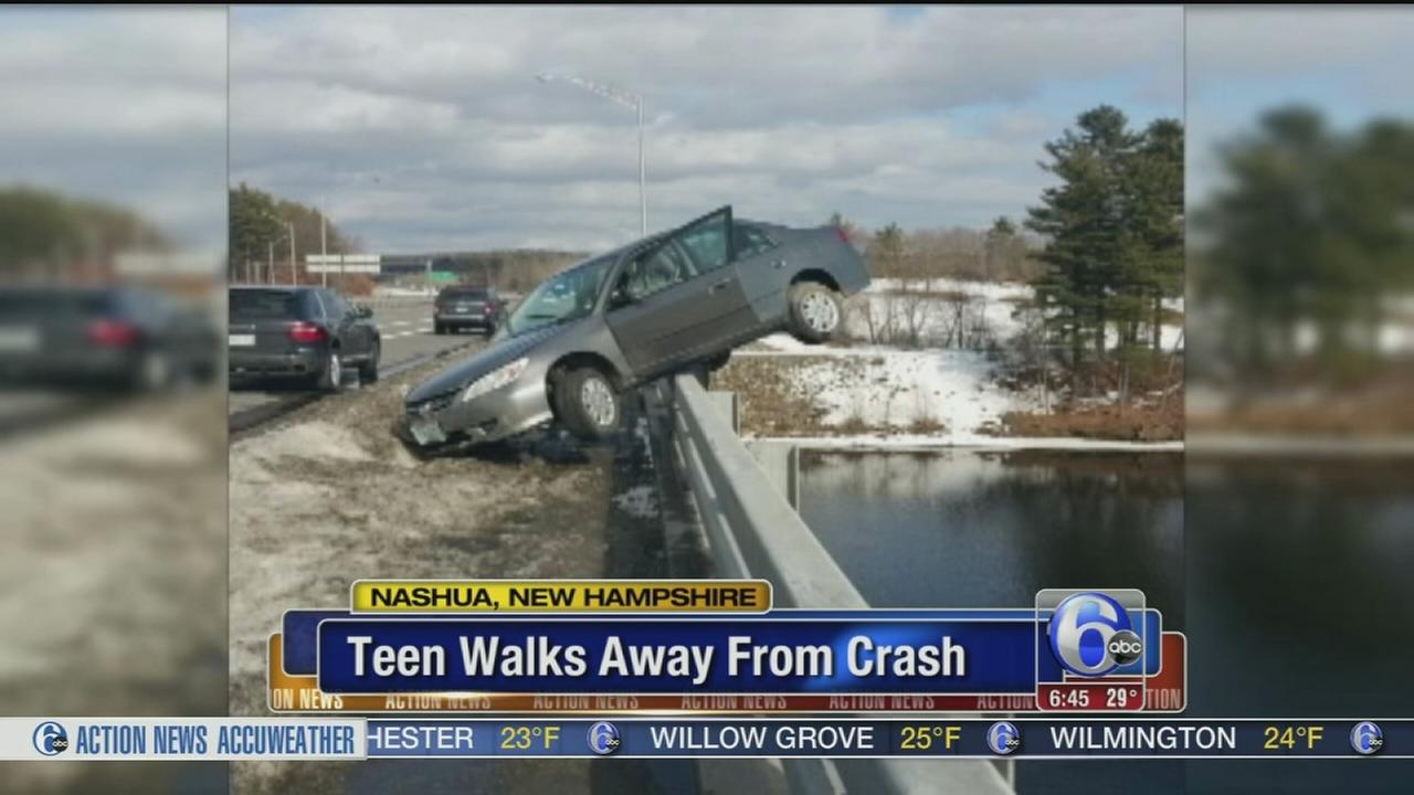 VIDEO: Car hits snow bank, dangles from bridge