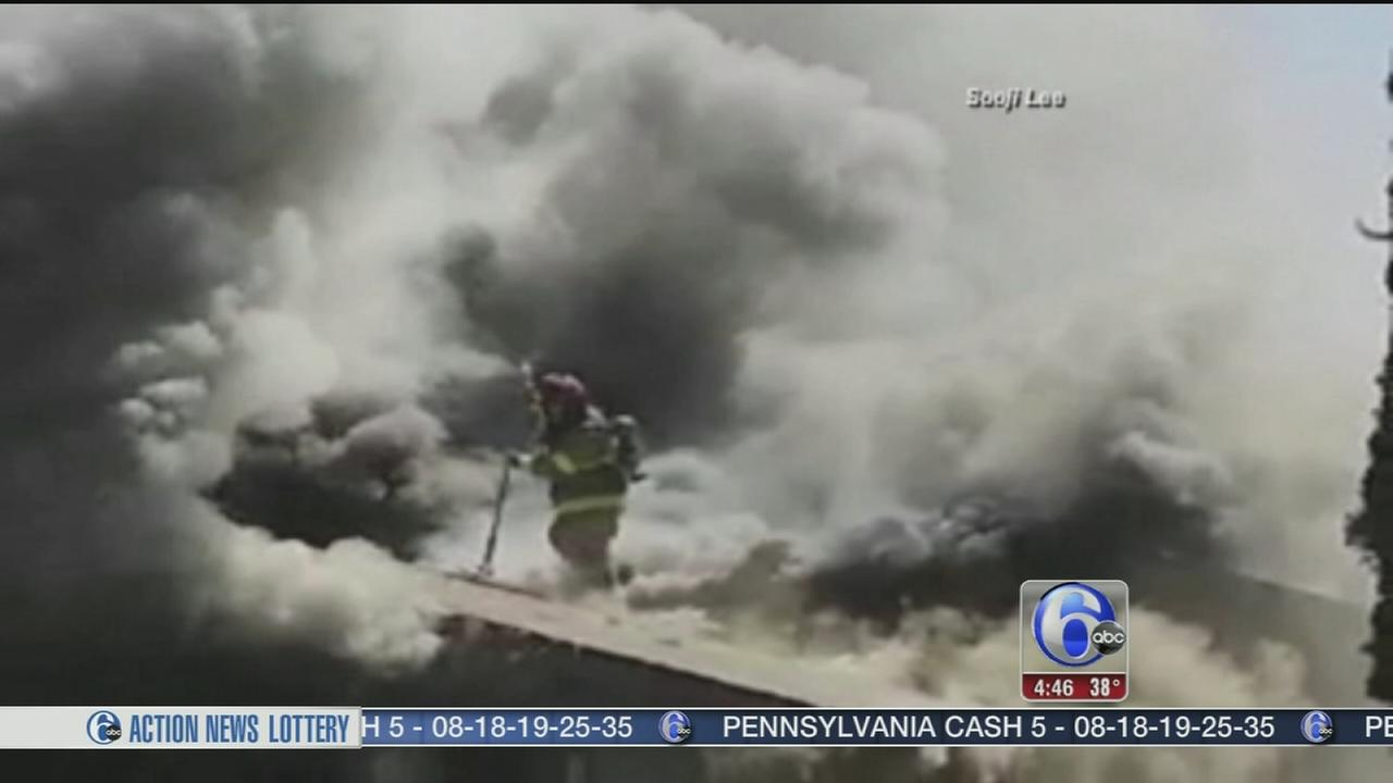 VIDEO: Firefighter falls through roof of burning home