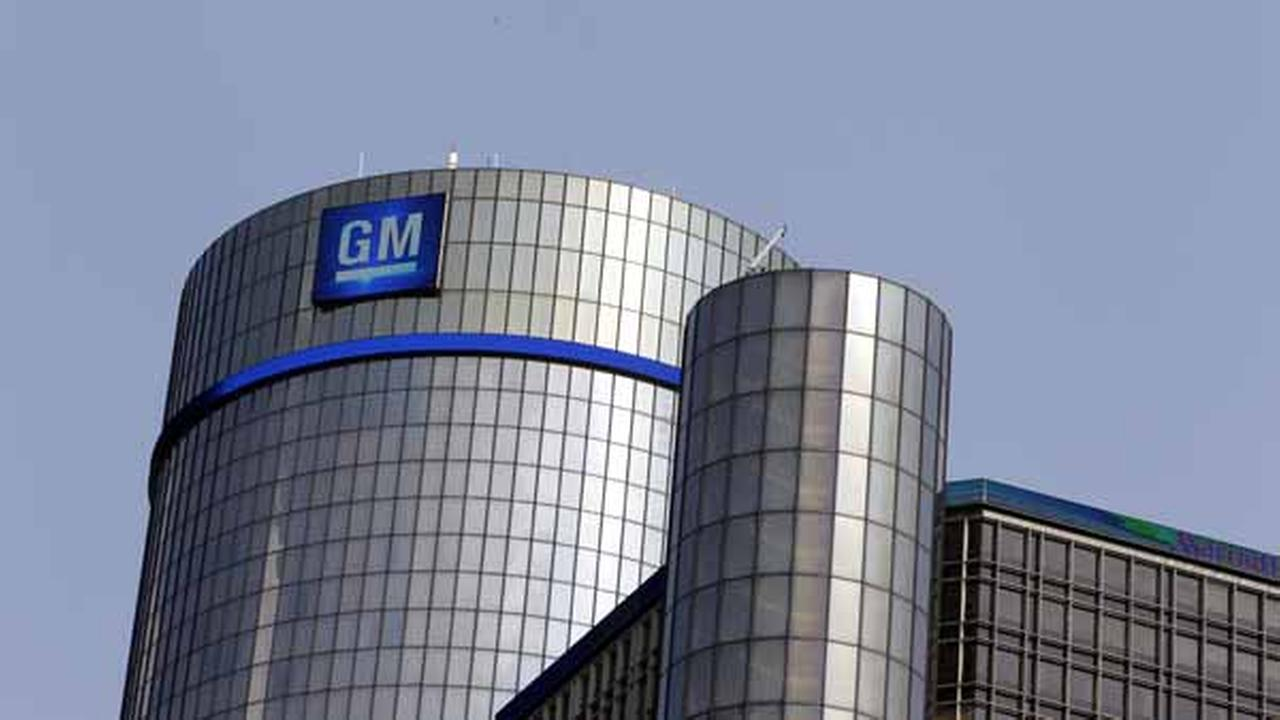 The General Motors logo and a blue light band are displayed atop the Renaissance Center in Detroit.