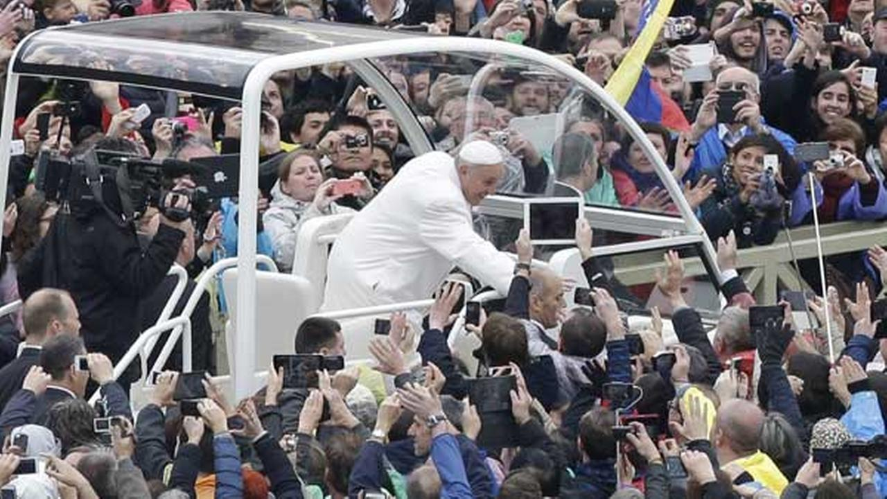 Pope Francis salutes faithful in St. Peters square at the Vatican, Sunday, April 5, 2015.