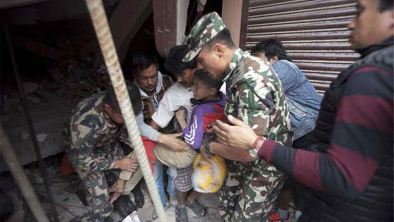 Volunteers carry an injured boy after rescuing him from the debris of a building that was damaged in an earthquake in Kathmandu, Nepal