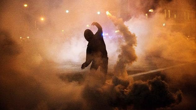 A protester throws a tear gas canister back toward riot police after a 10 p.m. curfew went into effect in the wake of Monday's riots following the funeral for Freddie Gray. <span class=meta>AP Photo/David Goldman</span>