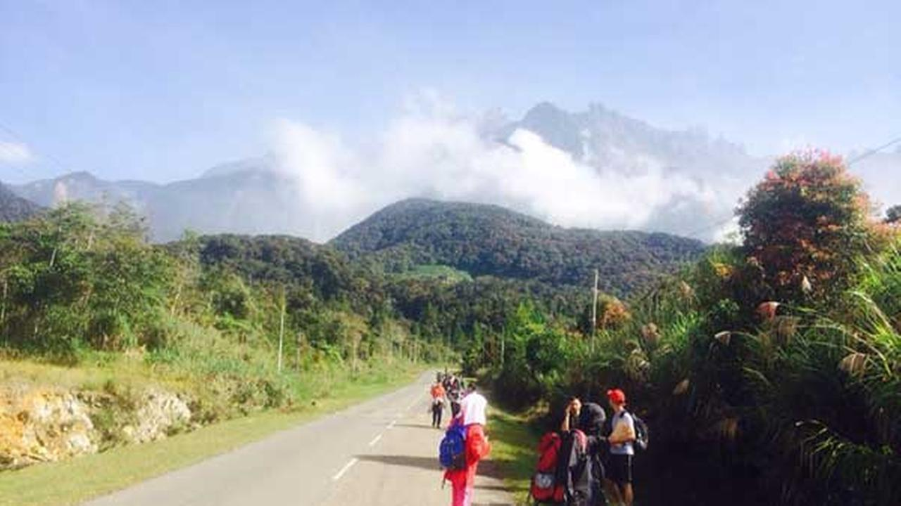 Tourists walk away from Mount Kinabalu hours after a magnitude 5.9 earthquake shook the area in Kundasang, Sabah, Malaysia, Friday, June 5, 2015.