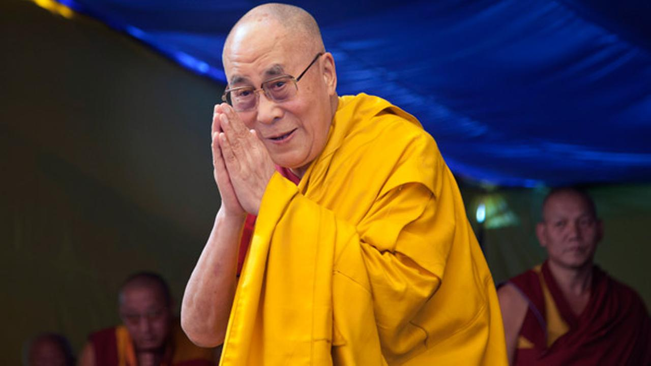 Tibetan spiritual leader the Dalai Lama greets devotees as he arrives to give a religious talk at the Tibetan Childrens Village School in Dharmsala, India, Wednesday, May 27, 2015