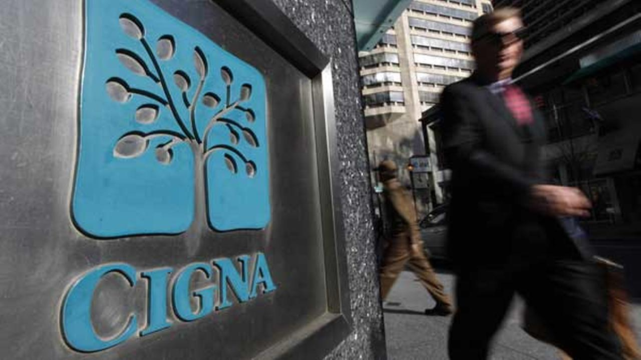 FILE - In this file photo, a pedestrian walks past the headquarters of the health insurer Cigna Corp. in in Philadelphia.
