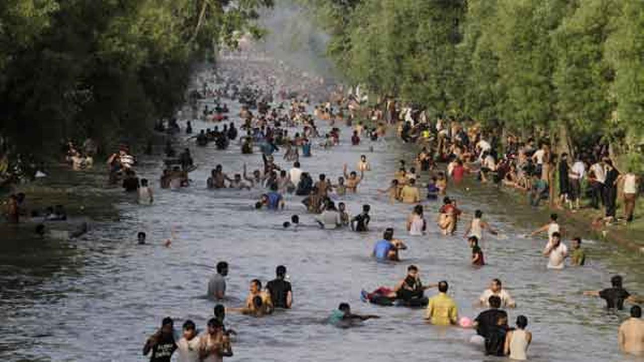 People cool off themselves in a canal in Lahore, Pakistan, where temperature reached 42 degrees Celsius (107.6 Fahrenheit), Sunday, June 7, 2015.