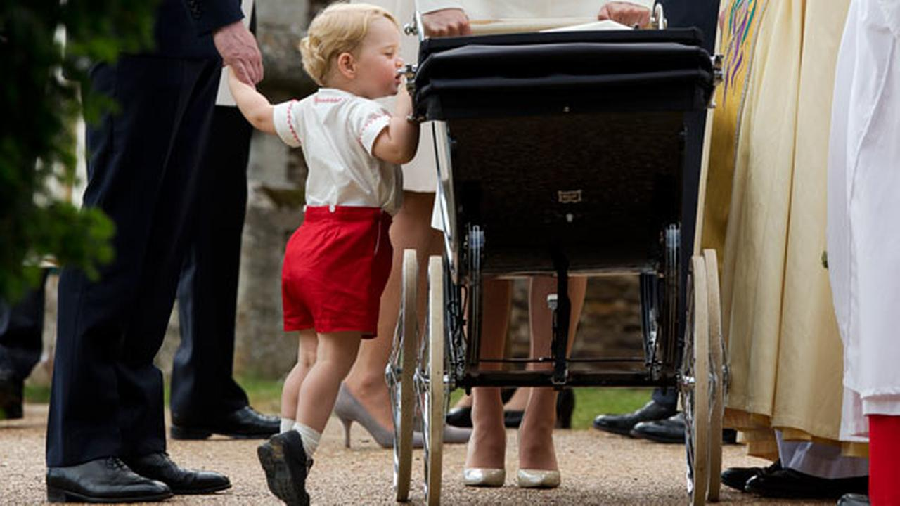 Britains Prince George gets up on tiptoes to peek into the pram of Princess Charlotte flanked by his parents Prince William and Kate the Duchess of Cambridge.