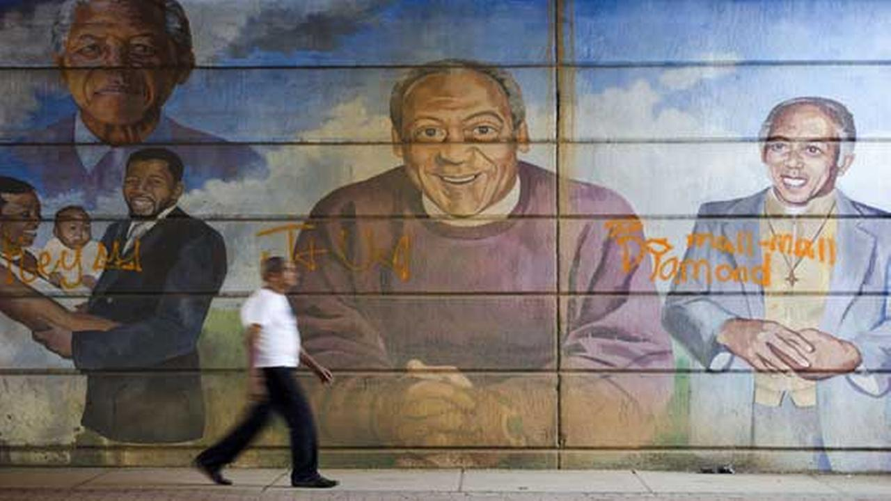 FILE - In this Wednesday, July 8, 2015 file photo, a man walks past a mural depicting entertainer Bill Cosby, center, in Philadelphia.