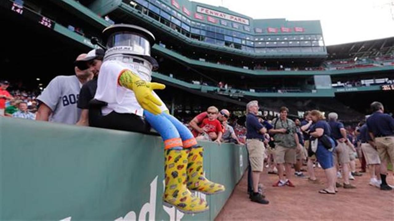 HitchBOT rests on the wall along the first base line before a baseball game at Fenway Park between the Boston Red Sox and Detroit Tigers in Boston, Friday, July 24, 2015.