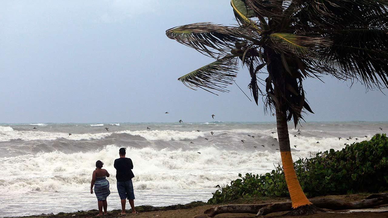 A couple looks out at a rough sea as Tropical Storm Erika moves away from the area in Guayama, Puerto Rico, Friday, Aug. 28, 2015 (AP Photo/Ricardo Arduengo)