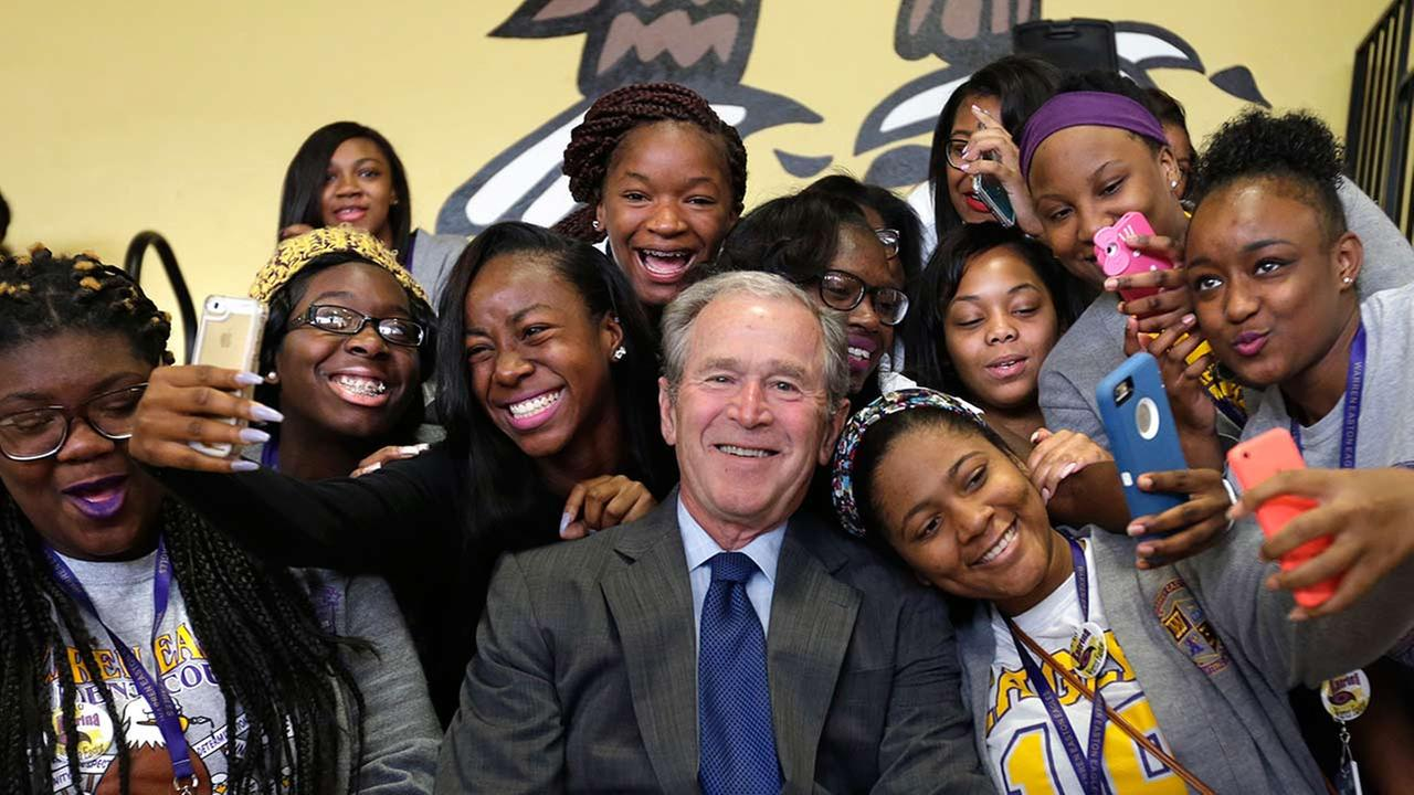 Former President George W. Bush poses for photos with students at Warren Easton Charter High School in New Orleans, Friday, Aug. 28, 2015.  (AP Photo/Gerald Herbert)