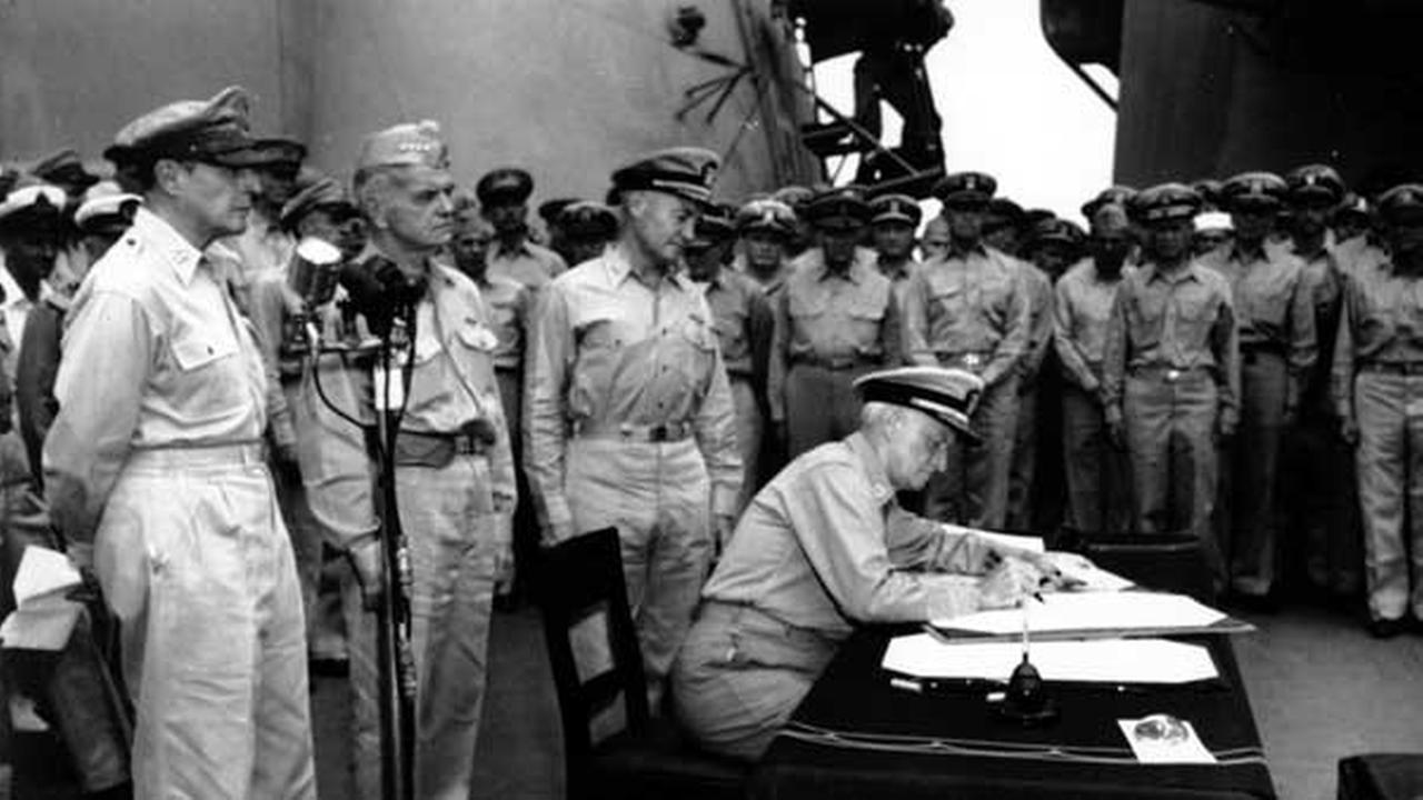 Admiral Chester W. Nimitz, Commander-in Chief of the Pacific Fleet, sat at the table aboard the Battleship Missouri as he signed the World War II surrender of the Japanese.
