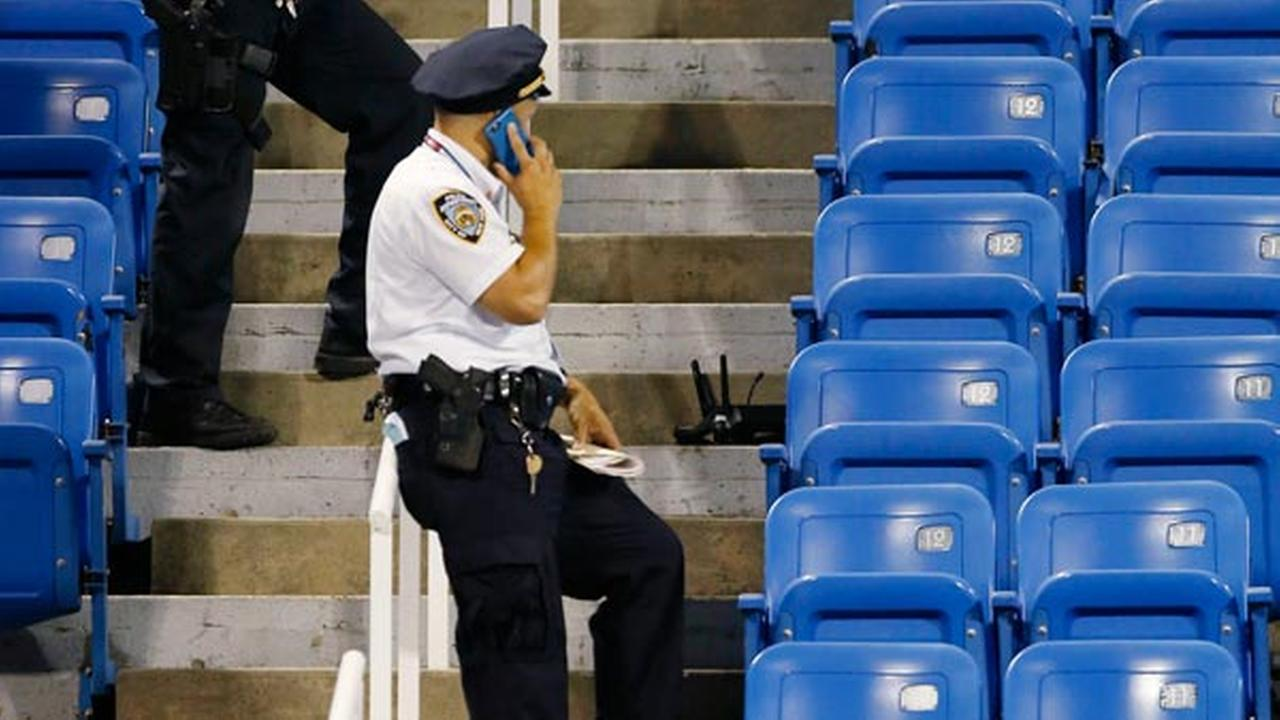 Police officers investigate the southwest corner of Louis Armstrong Stadium after a drone flew over the court, buzzing the players during a match.