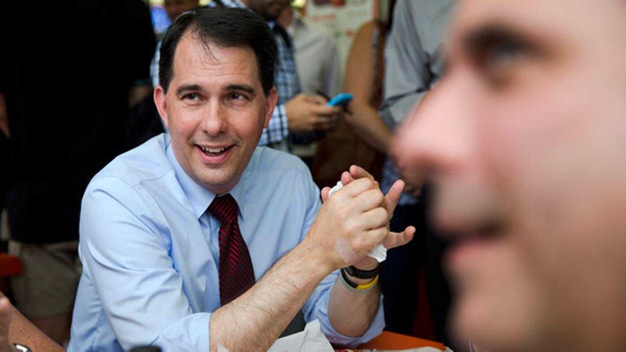 Republican presidential candidate, Wisconsin Gov. Scott Walker meets with voters, Tuesday, July 28, 2015, during a campaign stop at Genos Steaks in Philadelphia.