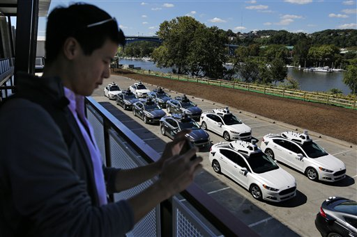 <div class='meta'><div class='origin-logo' data-origin='AP'></div><span class='caption-text' data-credit='AP Photo/Gene J. Puskar)'>Washington Post reporter Brian Fung watches as a group of self driving Uber vehicles position themselves to take journalists on rides.</span></div>