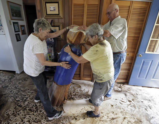 "<div class=""meta image-caption""><div class=""origin-logo origin-image none""><span>none</span></div><span class=""caption-text"">Harriet Oglesby, left, and her husband Hugh, right, help Bobbi Pattison stand up a sea captain statue carved out of wood from a 1993 storm  Friday, Sept. 2, in Steinhatchee, Fla. (AP)</span></div>"
