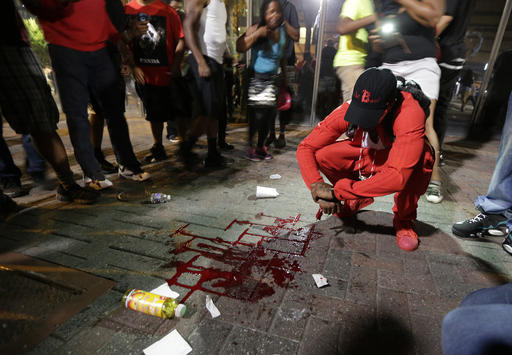 "<div class=""meta image-caption""><div class=""origin-logo origin-image none""><span>none</span></div><span class=""caption-text"">A man squats near a pool of blood after a man was injured during a protest of Tuesday's fatal police shooting of Keith Lamont Scott in Charlotte, N.C. on Wednesday, Sept. 21, 2016. (AP)</span></div>"