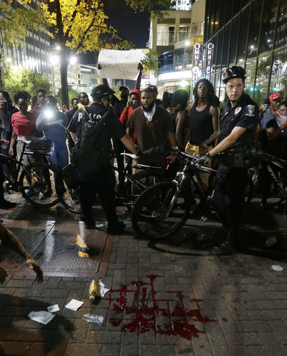 "<div class=""meta image-caption""><div class=""origin-logo origin-image none""><span>none</span></div><span class=""caption-text"">Polkce circle an area where a pool of blood lies after a man was injured during a protest of Tuesday's fatal police shooting of Keith Lamont Scott in Charlotte, N.C. (AP)</span></div>"