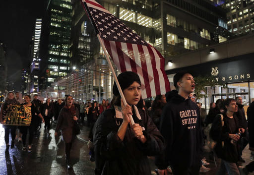<div class='meta'><div class='origin-logo' data-origin='AP'></div><span class='caption-text' data-credit='AP Photo/Julie Jacobson'>A protester carries an upside down American flag as she walks along Sixth Avenue while demonstrating against President-elect Donald Trump, Wednesday, Nov. 9, 2016, in New York.</span></div>