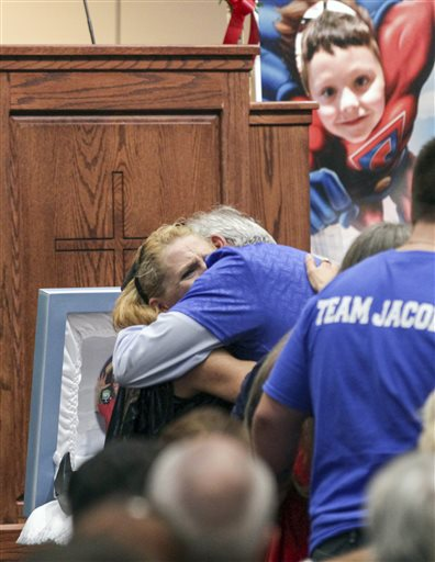<div class='meta'><div class='origin-logo' data-origin='none'></div><span class='caption-text' data-credit='Ken Ruinard/The Independent-Mail via AP, Pool'>Renae Hall, left, mother of Jacob Hall, hugs friends and family during a wake service for Jacob Hall.</span></div>