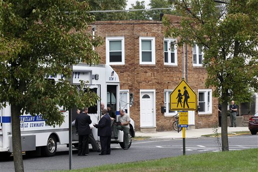 <div class='meta'><div class='origin-logo' data-origin='none'></div><span class='caption-text' data-credit='AP'>Police and other officials gather near a small brick apartment building where authorities say a 3-year-old boy was reported missing and then found dead.</span></div>
