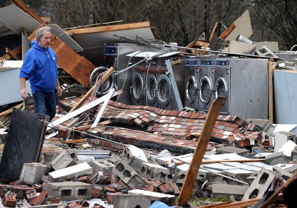 <div class='meta'><div class='origin-logo' data-origin='AP'></div><span class='caption-text' data-credit='Steve Helber'>Laundromat manager Brad Poindexter, of Danville, Va., walks over bricks at his damaged business after a deadly storm that swept through Waverly, Va., Wednesday, Feb. 24.</span></div>