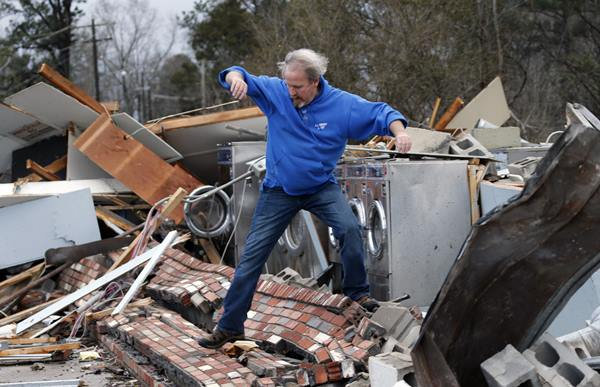 <div class='meta'><div class='origin-logo' data-origin='AP'></div><span class='caption-text' data-credit='Steve Helber'>Laundromat manager Brad Poindexter, of Danville, Va., jumps over bricks at his damaged business after a deadly storm that swept through Waverly, Va., Wednesday, Feb. 24, 2016</span></div>
