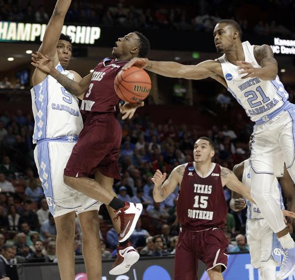 <div class='meta'><div class='origin-logo' data-origin='AP'></div><span class='caption-text' data-credit='AP Photo/Chuck Burton'>UNC's Seventh Woods (21) blocks a shot by Texas Southern's Demontrae Jefferson (3) as Tony Bradley (5) defends during the first half in a first-round NCAA Tournament game</span></div>