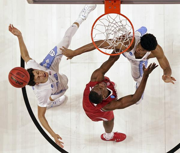 <div class='meta'><div class='origin-logo' data-origin='AP'></div><span class='caption-text' data-credit='AP Photo/Chuck Burton'>North Carolina's Justin Jackson, left, and Isaiah Hicks, right, battle Arkansas' Moses Kingsley, center for a rebound during the second half in a second-round game</span></div>