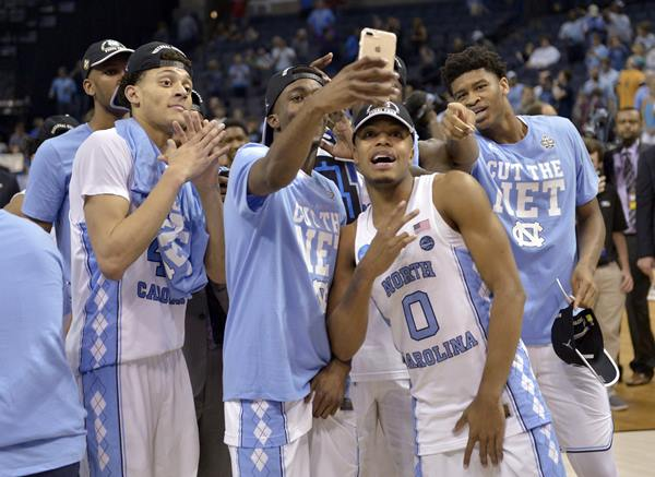 <div class='meta'><div class='origin-logo' data-origin='AP'></div><span class='caption-text' data-credit='AP Photo/Brandon Dil'>North Carolina players celebrate after beating Kentucky in the South Regional final game in the NCAA college basketball tournament</span></div>