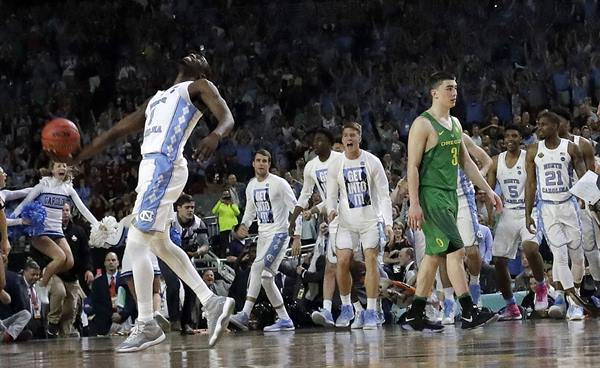 <div class='meta'><div class='origin-logo' data-origin='AP'></div><span class='caption-text' data-credit='AP Photo/David J. Phillip'>North Carolina's Theo Pinson (1) celebrates as Oregon's Payton Pritchard (3) walks off the court after the semifinals of the Final Four NCAA college basketball tournament</span></div>