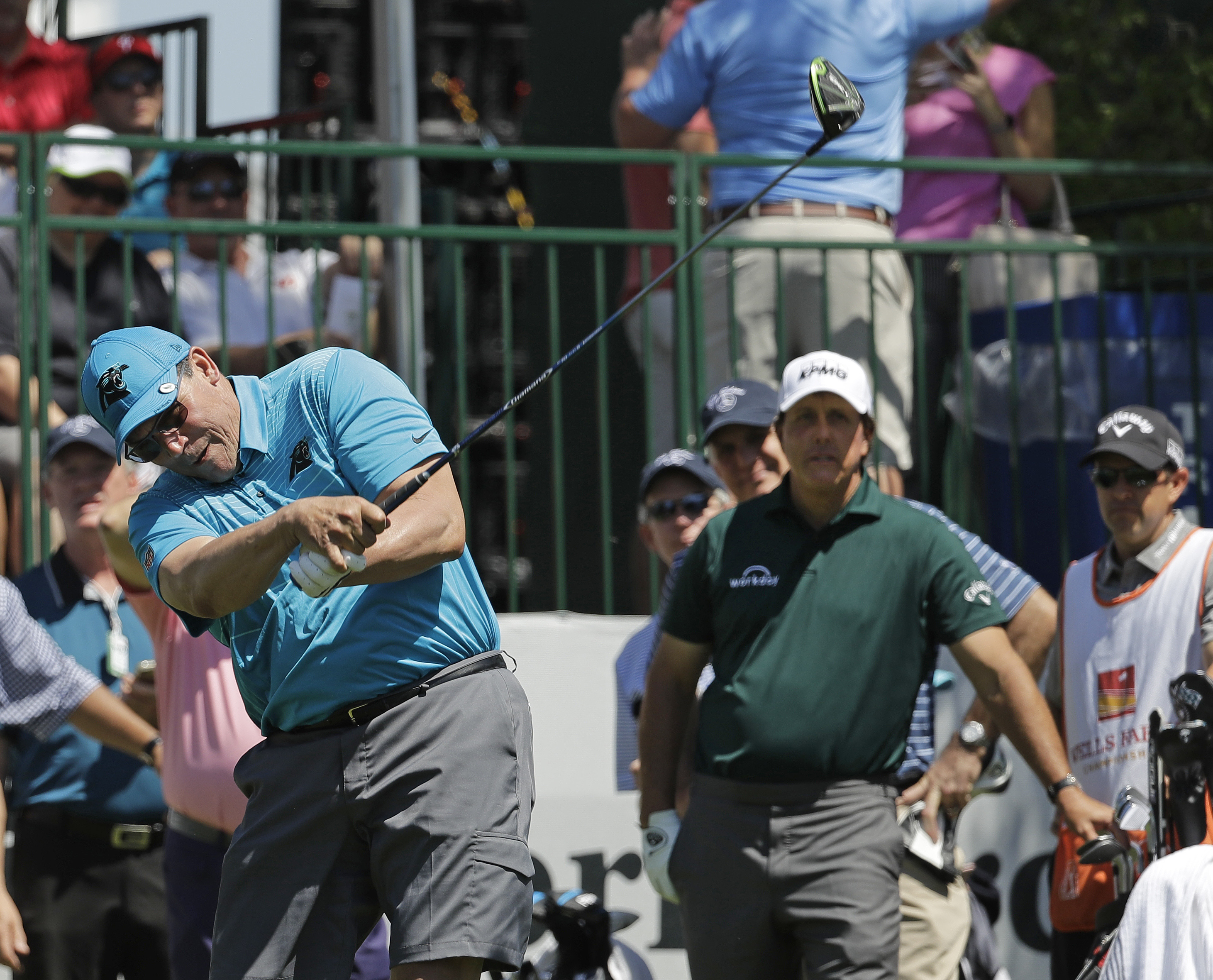 <div class='meta'><div class='origin-logo' data-origin='AP'></div><span class='caption-text' data-credit='Chuck Burton'>Carolina Panthers head coach Ron Rivera, left, hits his tee shot as Phil Mickelson, right, watches on the 10th hole.</span></div>