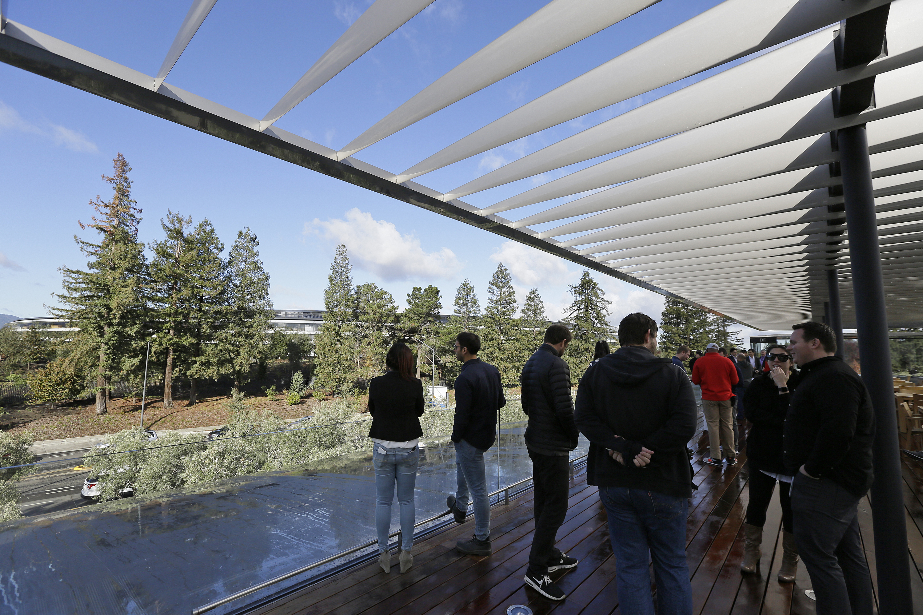 <div class='meta'><div class='origin-logo' data-origin='none'></div><span class='caption-text' data-credit='AP'>People stand on a rooftop terrace with the main building in the background during the grand opening of the Apple Park Visitor Center.</span></div>