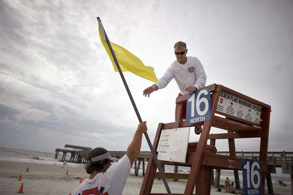 Tybee Island Ocean Rescue Senior Lifeguard Todd Horne, right, and Mark Eichenlaub, left, hang a yellow flag that warns swimmer of strong rip currents from Hurricane Arthur <span class=meta>AP / Stephen Morton</span>