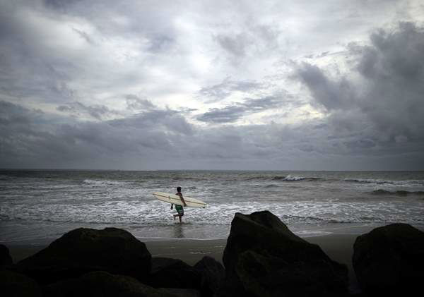Kevin Taylor of Savannah, Ga., heads out to surf the waves on the north beach of Tybee Island. <span class=meta>(AP &#47; Stephen Morton)</span>