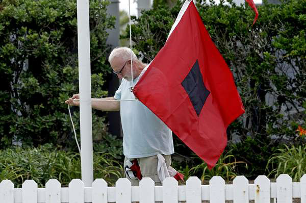"<div class=""meta ""><span class=""caption-text "">Bill Peters, innkeeper at the Cypress House Inn in Kill Devil Hills, N.C., prepares to raise a hurricane warning flag Thursday, July 3, 2014.  (AP / Gerry Broome)</span></div>"