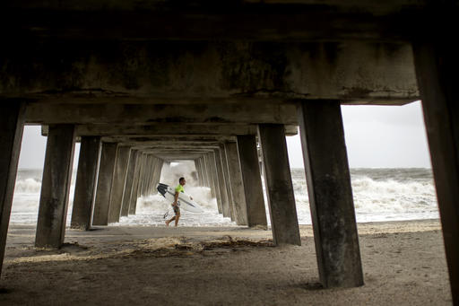 <div class='meta'><div class='origin-logo' data-origin='none'></div><span class='caption-text' data-credit=''>A surfer walks under a pier after surfing waves from the surge of Hurricane Hermineoff the coast of Tybee Island, Ga. (AP Photo/Stephen B. Morton)</span></div>
