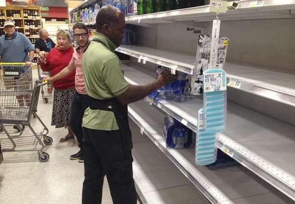 "<div class=""meta image-caption""><div class=""origin-logo origin-image ap""><span>AP</span></div><span class=""caption-text"">An employee restocks bottled water on bare shelves as customers look on at a Publix grocery store, Tuesday in Surfside, Fla. (Wilfredo Lee)</span></div>"