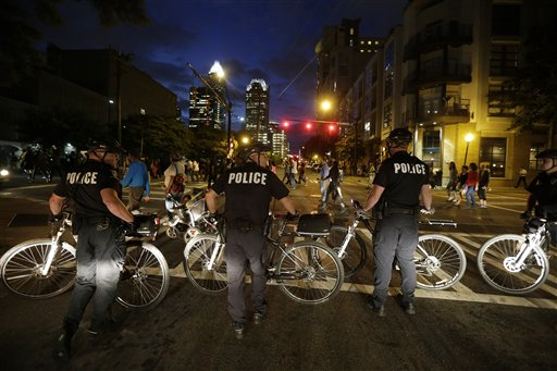 "<div class=""meta image-caption""><div class=""origin-logo origin-image none""><span>none</span></div><span class=""caption-text"">Demonstrators protest next to a police officer in Charlotte. (AP Photo/Chuck Burton)</span></div>"