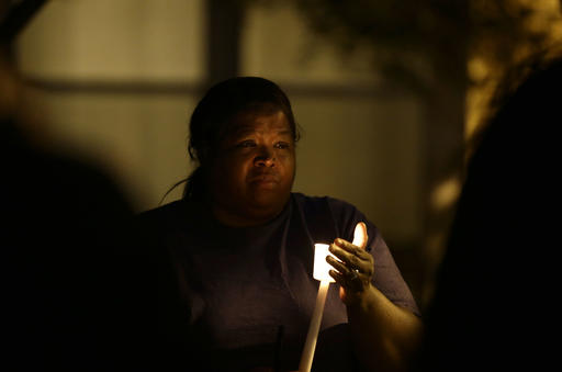 <div class='meta'><div class='origin-logo' data-origin='none'></div><span class='caption-text' data-credit=''>A woman holds a candle as people gather for a vigil in Charlotte. (AP Photo/Gerry Broome)</span></div>