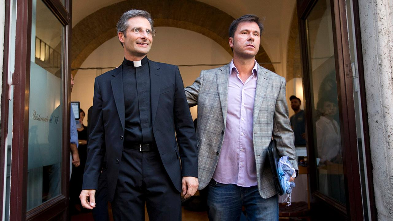 Monsignor Krzysztof Charamsa, left, and his boyfriend Eduard, surname not given, pose for a photo as they leave a restaurant after a news conference in downtown Rome