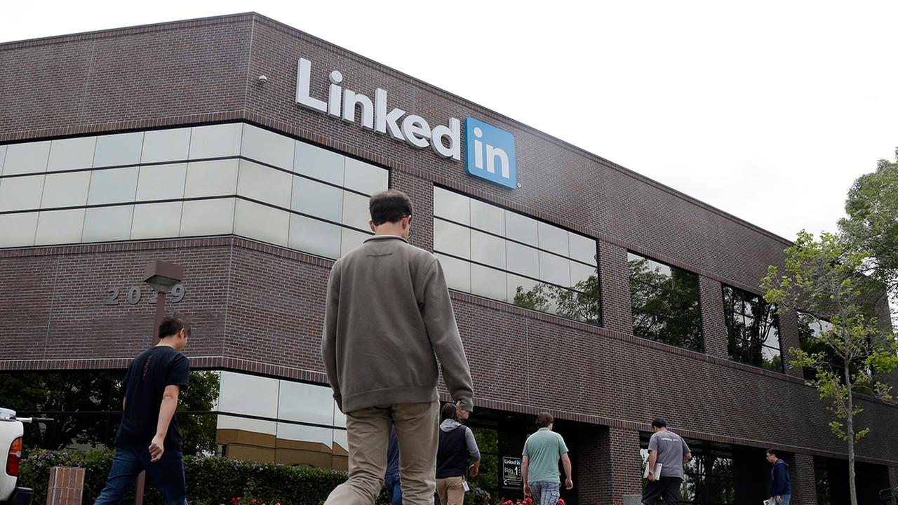 FILE - In this May 8, 2014 file photo, people walk outside of LinkedIn headquarters on in Mountain View , Calif.