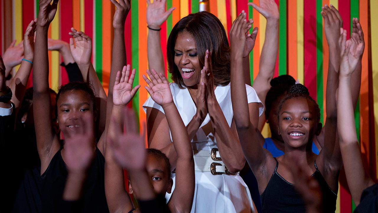 First lady Michelle Obama dances on stage with student performers as she and the Presidents Committee on the Arts and the Humanities  Tuesday, May 20, 2014 in the White House.