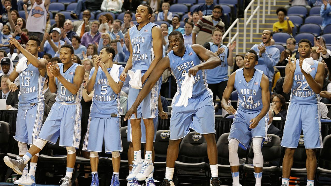 react after a teammate's basket against UNC Greensboro basketball ...