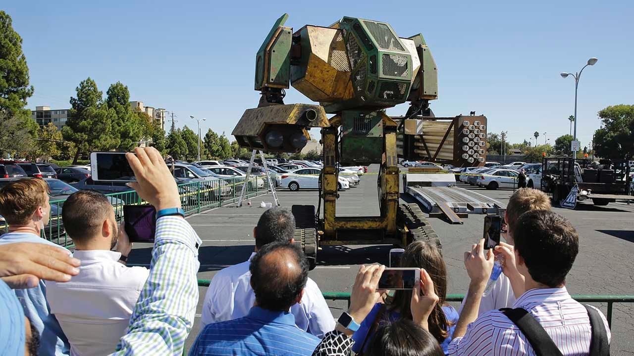 In this photo taken Friday, Oct. 9, 2015, a crowd of people watch the MegaBots 15-foot tall, piloted Mk.II robot in action at the Pioneer Summit in Redwood City, Calif.