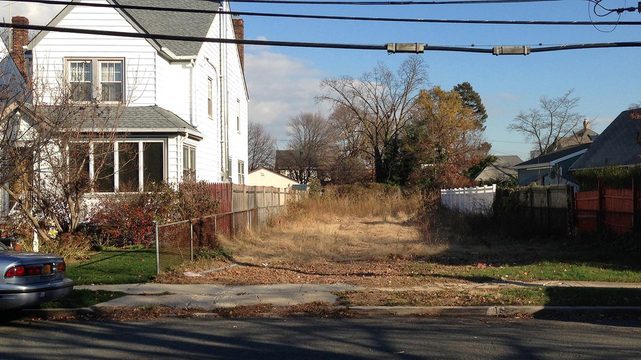 In this Nov. 25, 2015 photo, a lot stands empty in West Hempstead, N.Y., after the township had the home that once stood on it torn down.