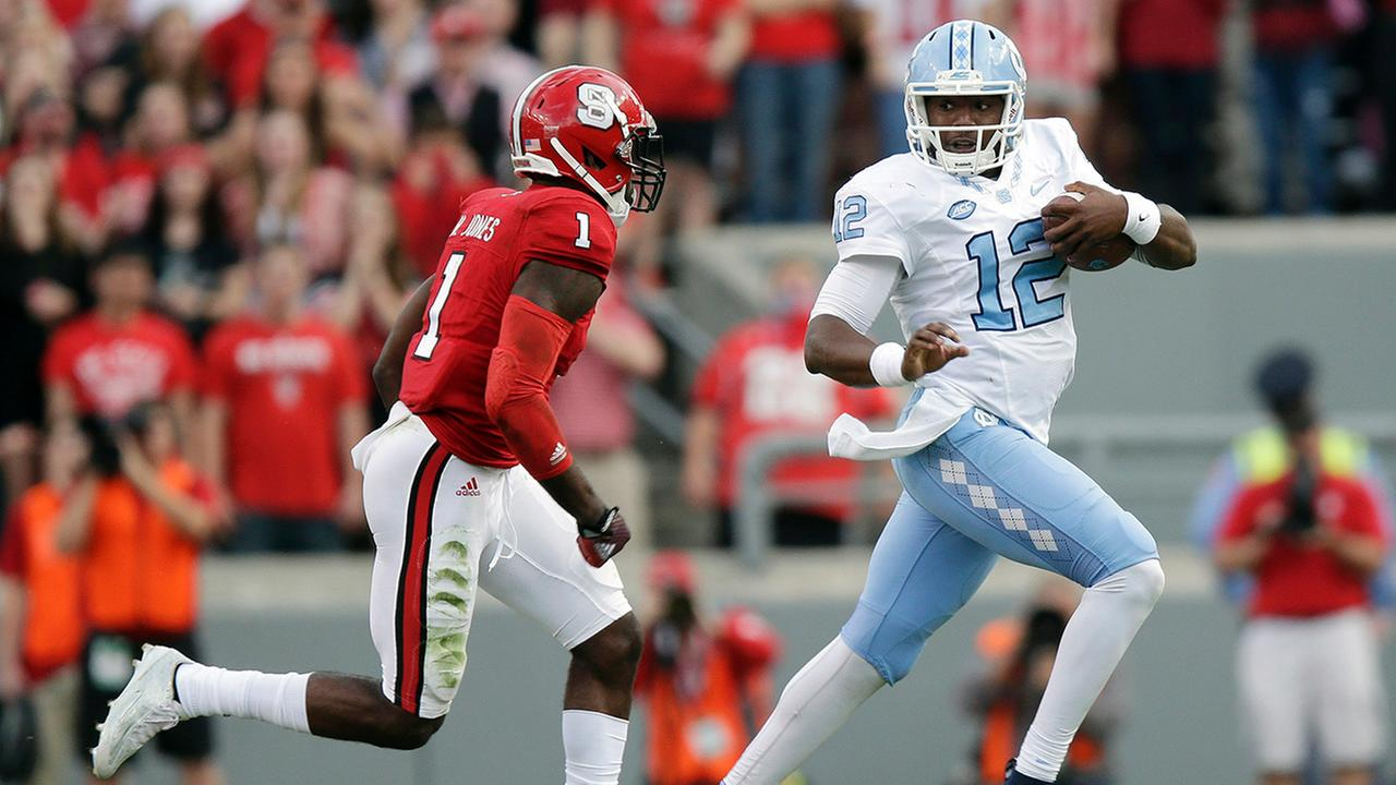 North Carolina quarterback Marquise Williams (12) runs the ball as North Carolina States Hakim Jones (1) chases during the first half