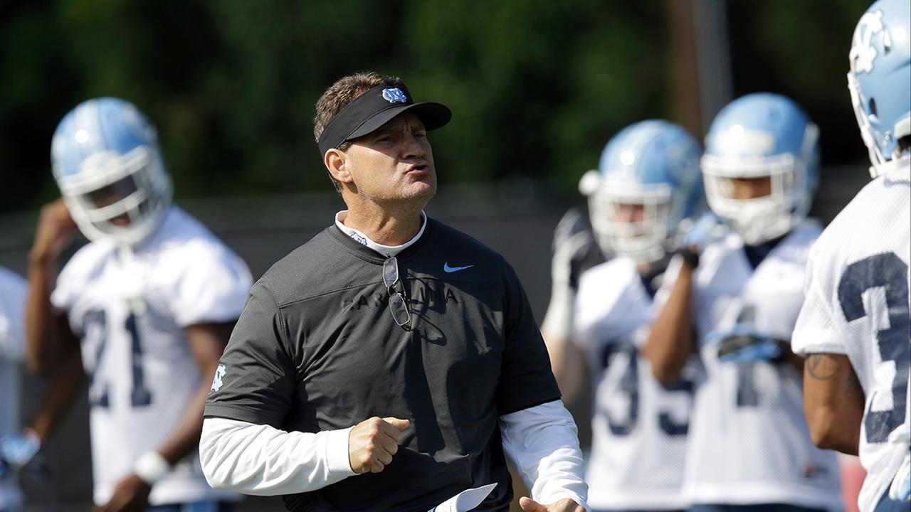 North Carolina defensive coordinator Gene Chizik works with players during the teams first NCAA college football practice of the season in Chapel Hill, N.C., Monday, Aug. 3, 2015.